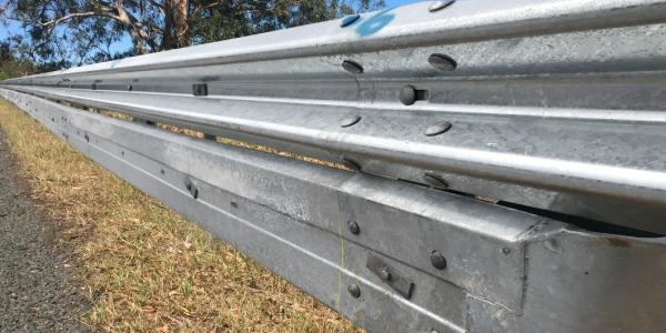 biker shield is attached below the w beam guardrail